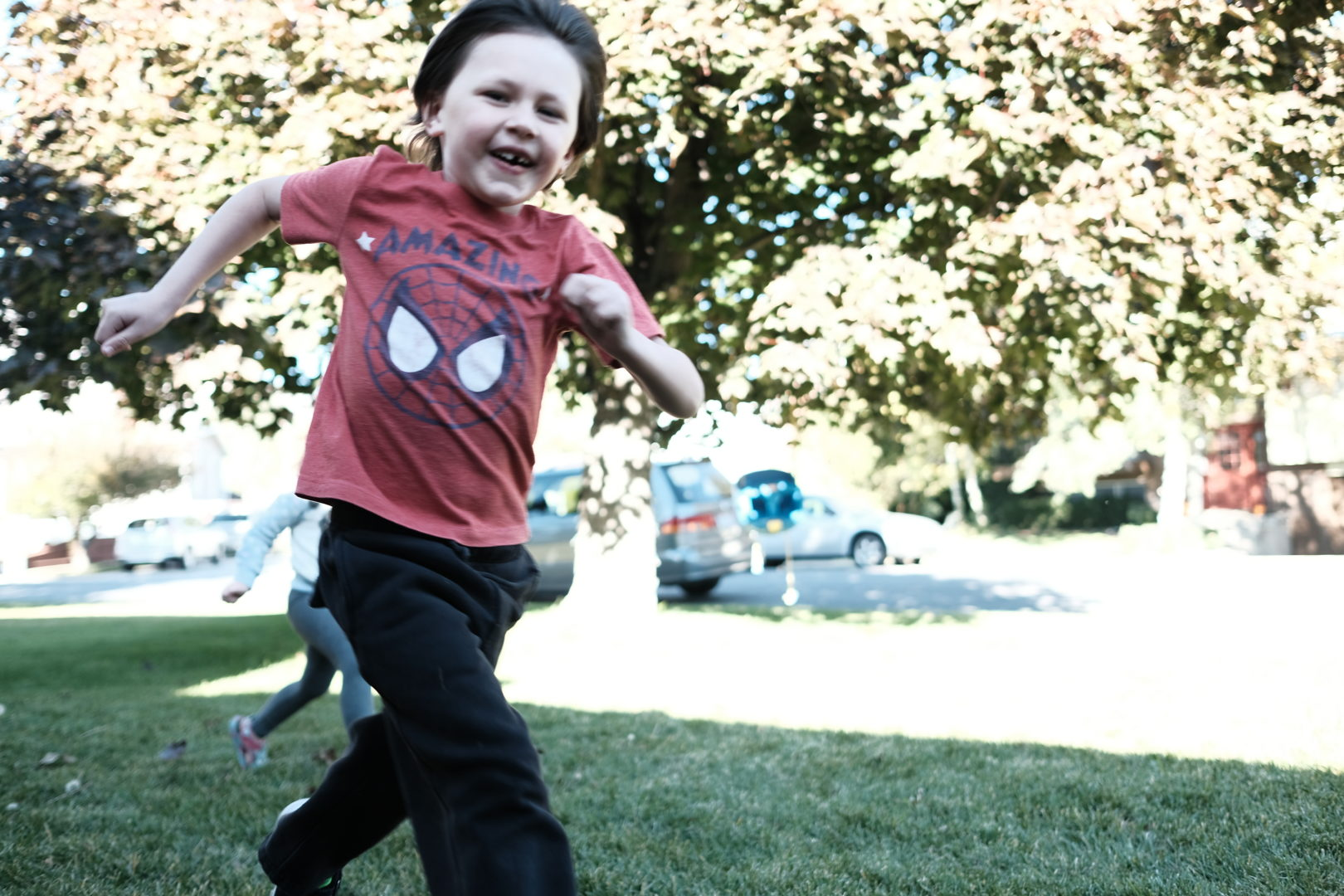 A smiling happy little boy runs past the camera