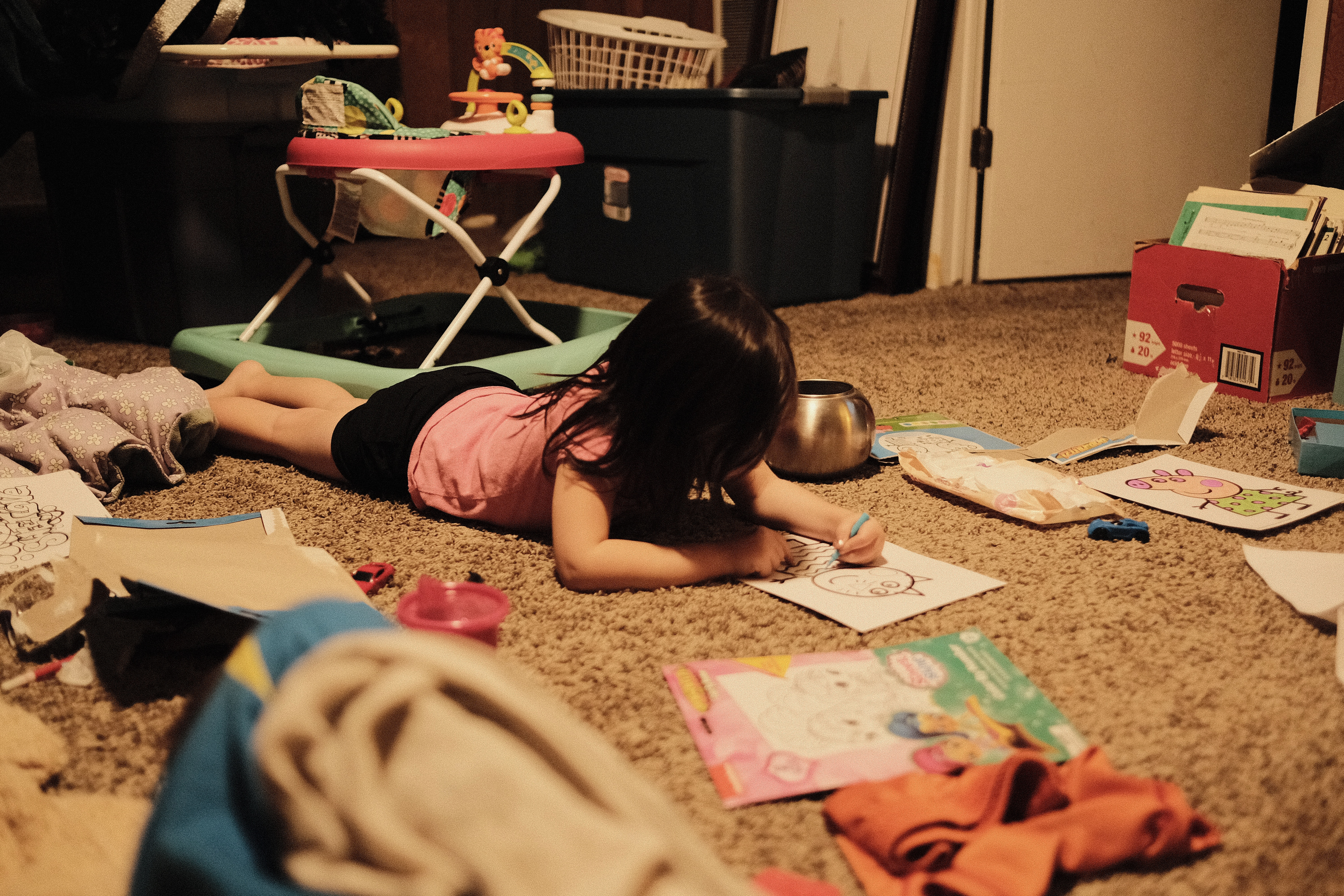 Elle laying on the floor coloring
