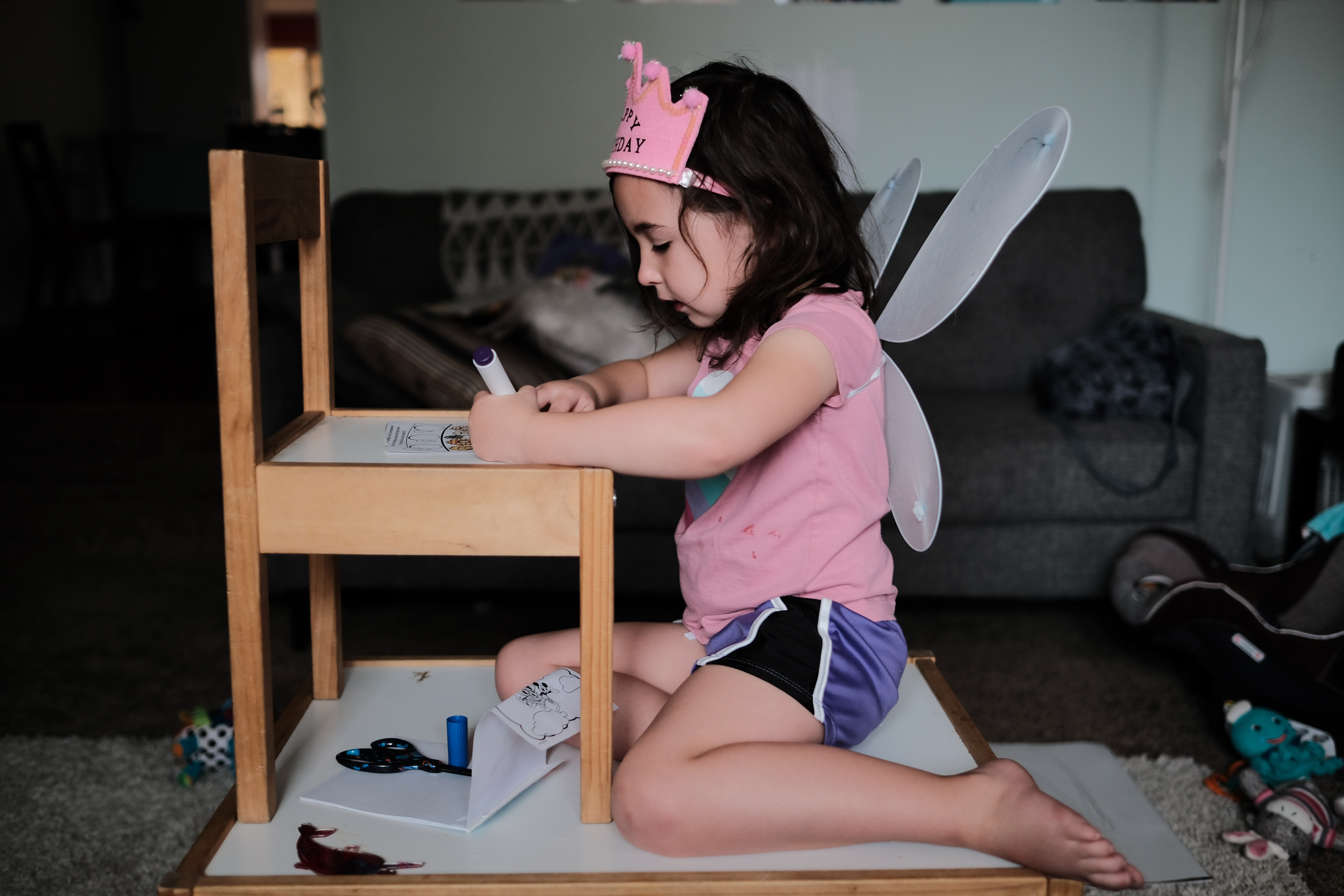 Elle sits on a table coloring on a chair.