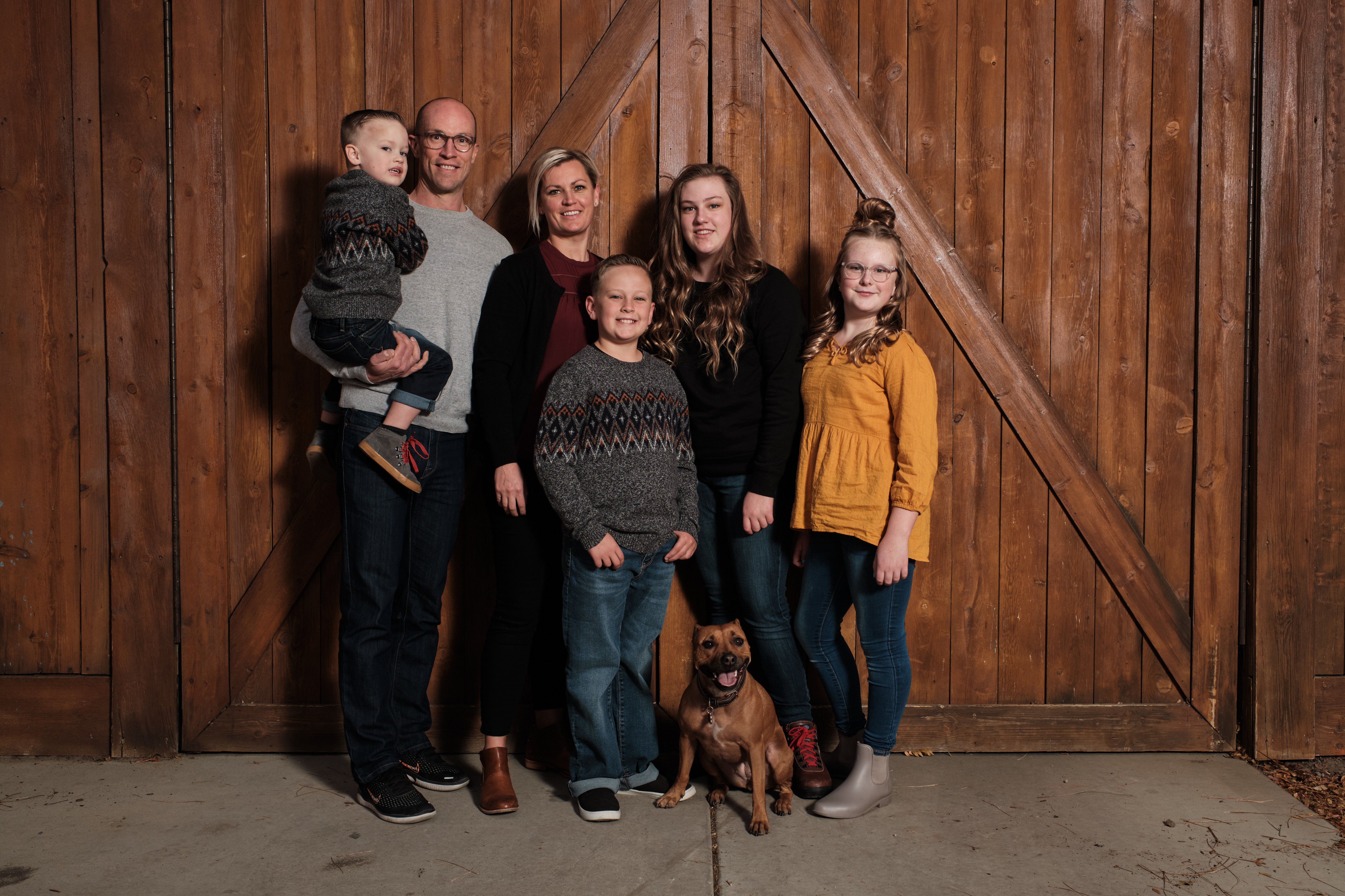 A family picture in front of a barn wall.