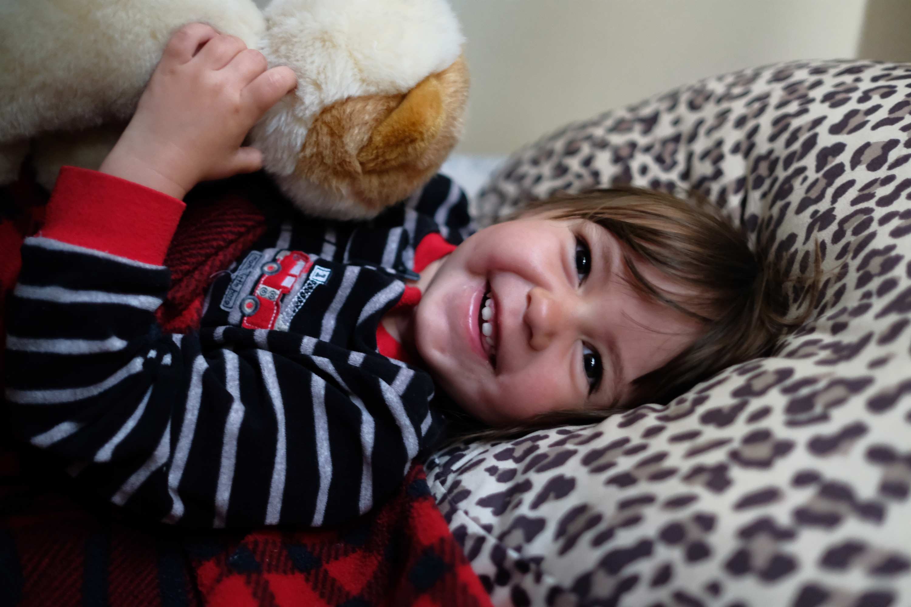 Emily laying in her bed smiling.